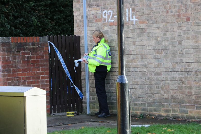 A police officer tapes up a gate giving access to the rear of the property